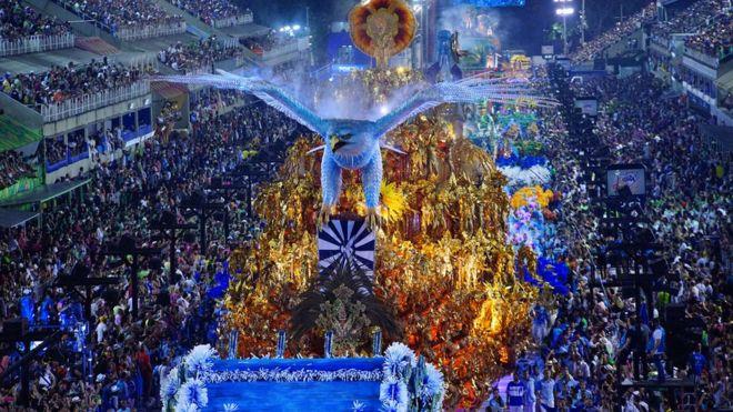 Águia azul gigante à frente de foliões com fantasias douradas no sambódromo do Rio