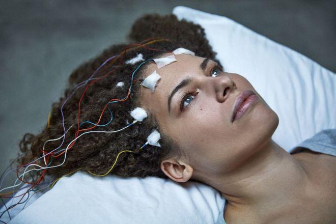 Primer plano de mujer tirada en la cama con cables en la cabeza