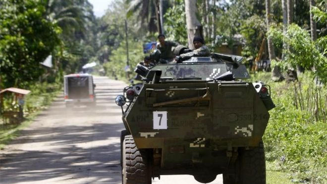 """Filipino soldiers in a military tank transit at a road on the outskirts of Jolo, Sulu Island, southern Philippines, 27 April 2016. The Armed Forces of the Philippines (AFP) and the Philippine National Police (PNP) vowed to """"neutralize"""" Abu Sayyaf terrorists after the beheading of a Canadian hostage, who was kidnapped from a resort in the southern Philippines along with three others in September."""