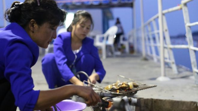 Two women grilling clams