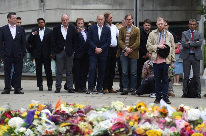People react as they look at flowers left on the south side of London Bridge near Borough Market