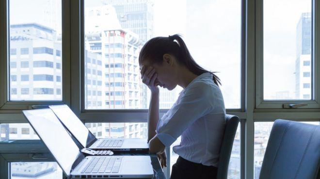 Mujer usando laptop y cubriéndose la cara con la mano.
