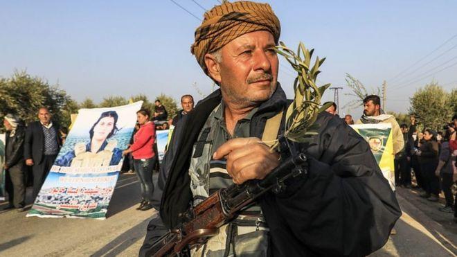Kürt bir savaşçı, Türkiye'nin Afrin'deki operasyonlarına karşı yapılan protestoya elinde tüfeği ve zeytin dalıyla katılırken