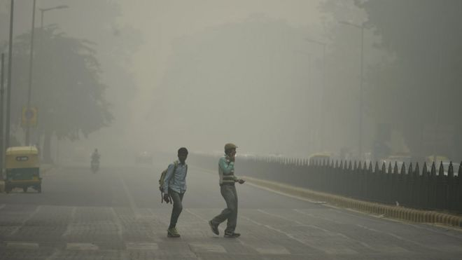 Two pedestrians on road in New Delhi engulfed in smog from last year