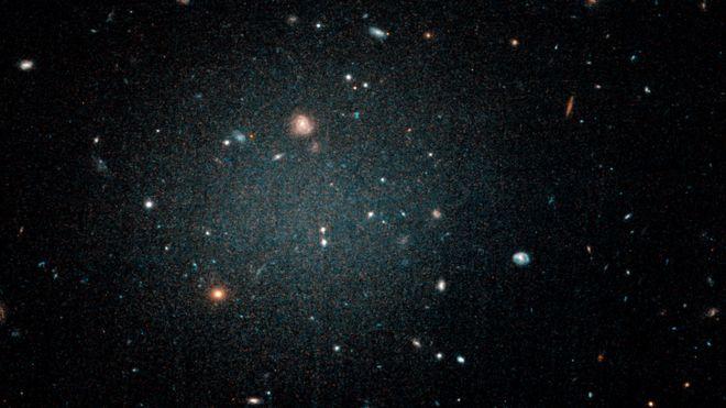 """Расплывчатый """"шарик"""" с другими галактиками позади него."""