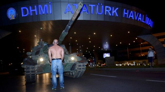 A man stands in front of a Turkish army tank at Ataturk airport in Istanbul