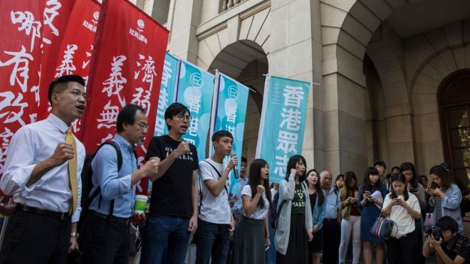 Pro-democracy activists Avery Ng (3rd L), Figo Chan (4th L) and Tiffany Yuen (C) shout slogans outside the Court of Final Appeal ahead of bail applications for jailed activists Joshua Wong and Nathan Law at Hong Kong's highest court in Hong Kong on October 24, 2017.