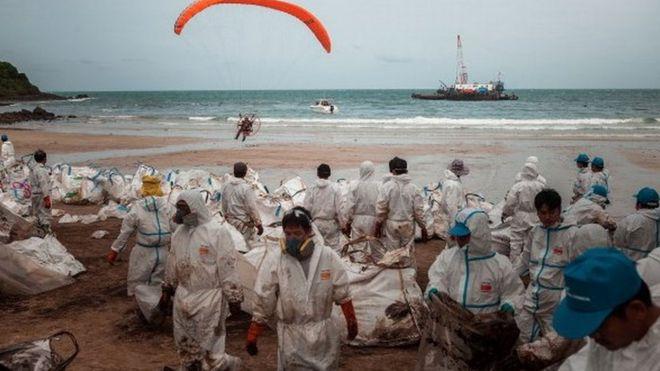 เจ้าหน้าที่กำลังทำความสะอาดหาดของเกาะเสม็ดหลังเกิดเหตุน้ำมันรั่วไหลครั้งใหญ่เมื่อปี 2556