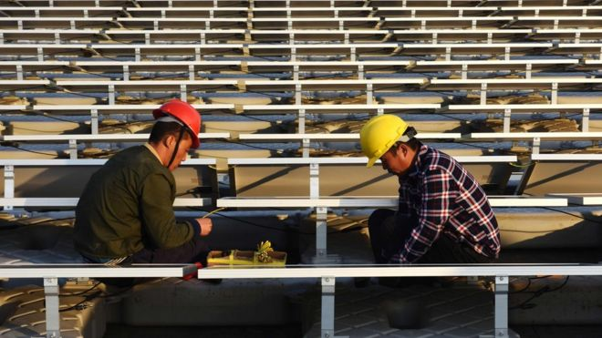 Men in hard hats work on a solar power plant in China