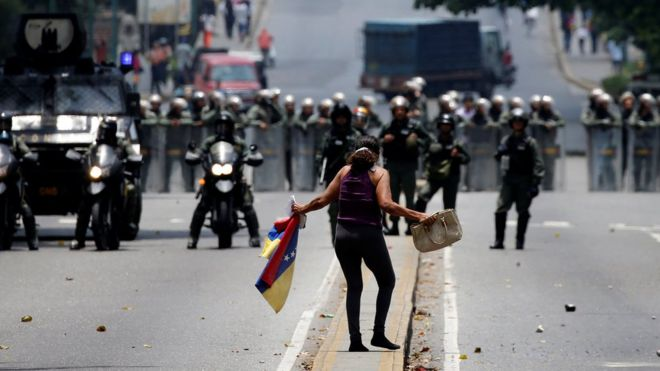 A demonstrator faces riot police at a rally against Venezuelan President Nicolas Maduro in Caracas, 20 April 2017