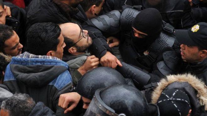 Une importante foule de manifestants contenue par des agents des forces de l'ordre.