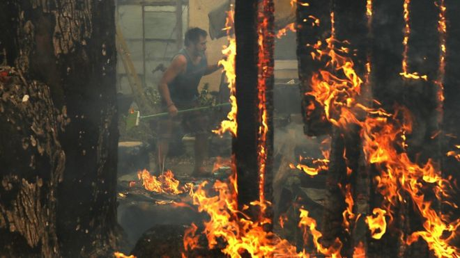 A man battles to save his home pictured through the flames