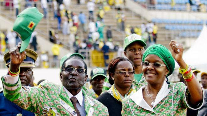 Zimbabwe's President Robert Mugabe (L) and his wife Grace (R) greet supporters after his address at a rally in Harare on July 28, 2013, ahead of elections on July 31.