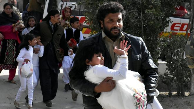 A bearded man carries a girl, dressed in white, from the scene of the attack
