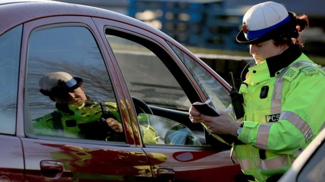 A policewoman stopping a driver