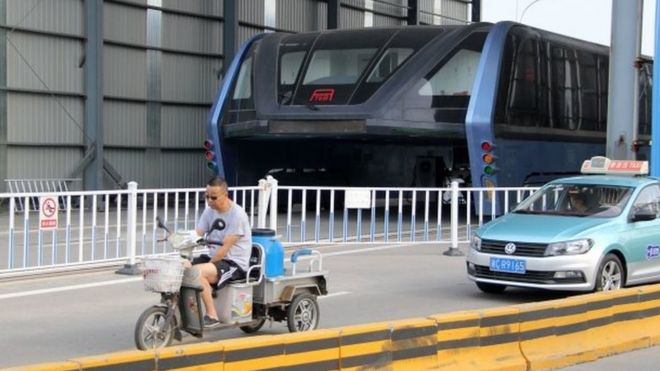 "A car drives past the Transit Elevated Bus (TEB) on Fumin road in Qinhuangdao city, north China""s Hebei province, 21 June 2017."