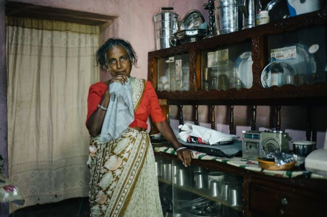 A tea plucker poses inside her house