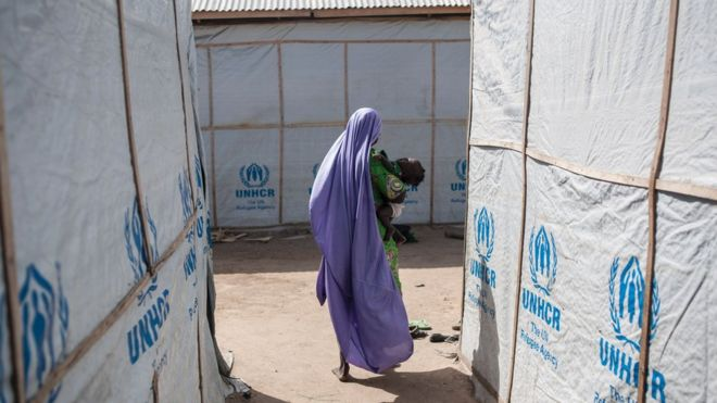 A woman carrying her baby walks through the temporary shelters provided by the Mission for the United Nations High Commissioner for Refugees (UNHCR) in one of the hosting communities in Maiduguri in northeastern Nigeria on December 7, 2016.