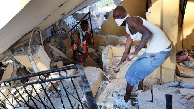 Hombre retira escombros en busca de supervivientes tras el terremoto de Haití en 2010.