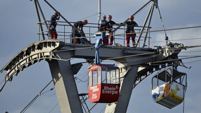 Firefighters assess the damage caused after a cable car struck a pillar in Cologne, Germany, 30 July 2017