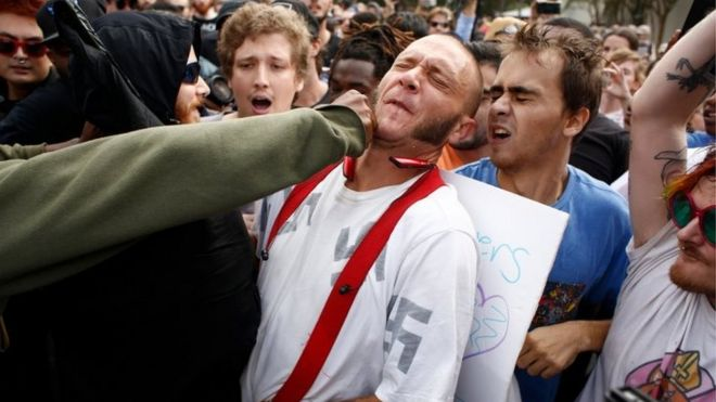 A man wearing a shirt with swastikas is punched by a member of a crowd of protesters at University of Florida's campus, where white nationalist Richard Spencer gave a speech.