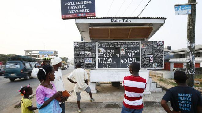 أشخاص ينظرون إلى لوحة بها أرقام لنتائج الانتخابات في ليبيريا