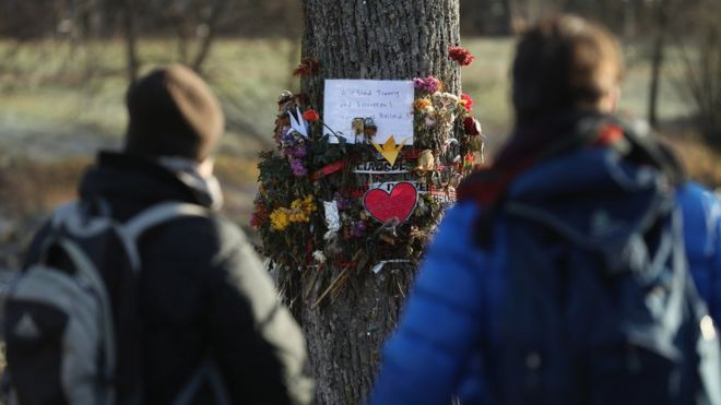 Passers-by stop to look at flowers and messages left by mourners in Freiburg