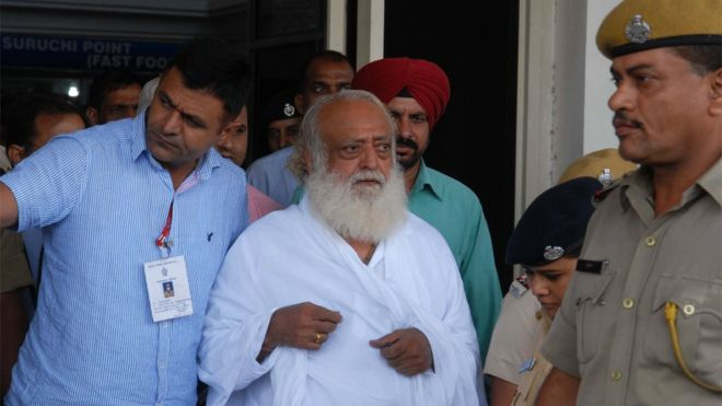ndian spiritual guru Asaram Bapu (C) is escorted by police, after he was arrested from his Indore ashram, at the airport in Jodhpur on September 1, 2013