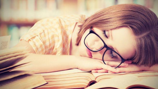 Mujer dormida sobre los libros