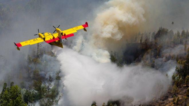 Испанский пожарный самолет сбрасывает воду на горящий лес, 18 июня 2017