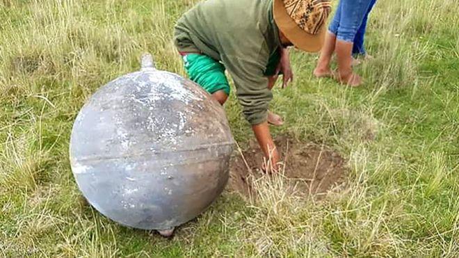 Homem mostra o buraco que se abriu na terra com a queda do objeto