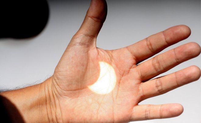 Güneş tutulmasının bir görüntüsü, 21 Ağustos 2017, Meksika, Baja California, Ensenada'da bir elin üzerine yansıtıldı.