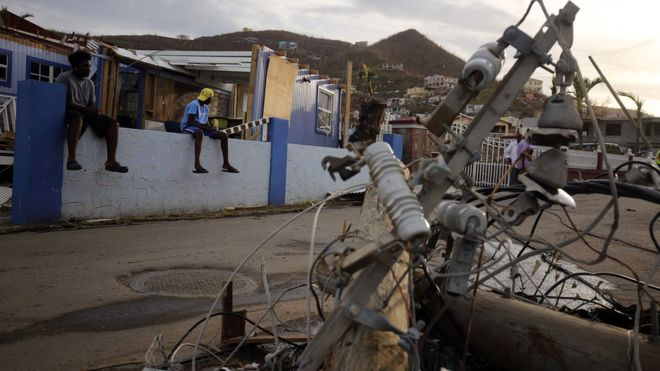 Residents look at downed power lines on British Virgin Islands