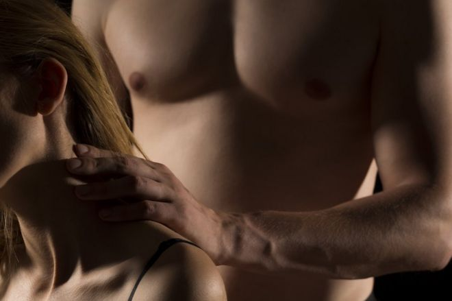 Man with a naked torso touches a woman's neck.