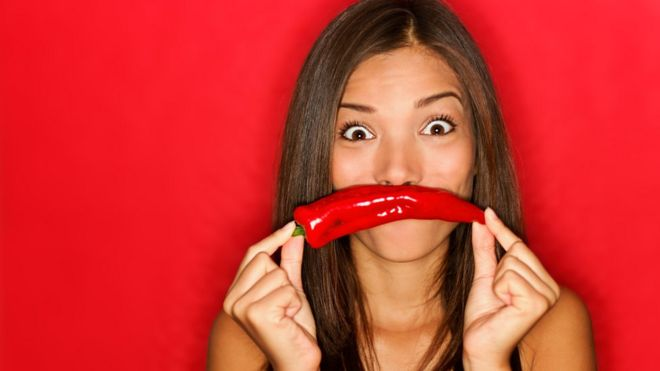 Mujer sosteniendo un pimiento en la boca.