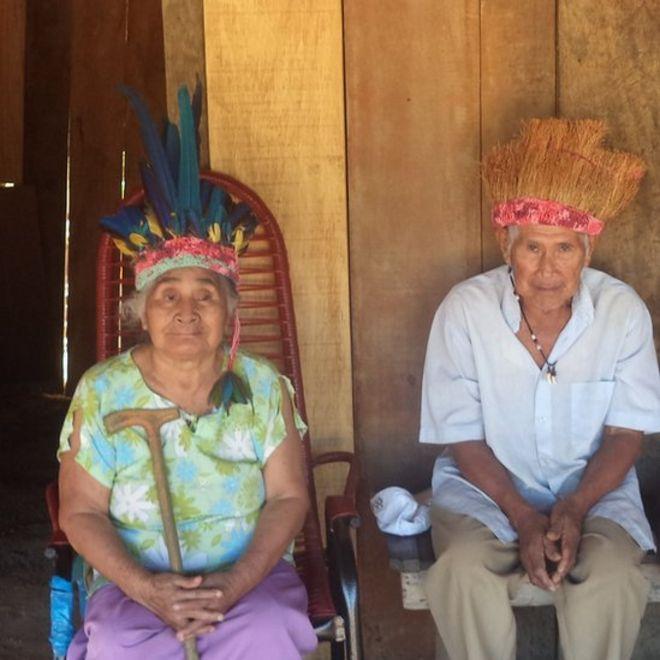 Os idosos Känä́tsɨ e Híwa, últimos falantes da língua warázu, sentados em frente à sua casa em RO, com a acessórios de seu povo indígena na cabeça