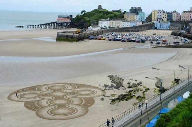 Nghệ sỹ Marc Treanor tạo tác phẩm trên cát ở bờ Bãi Bắc ở Cản Tenby tại Wales.