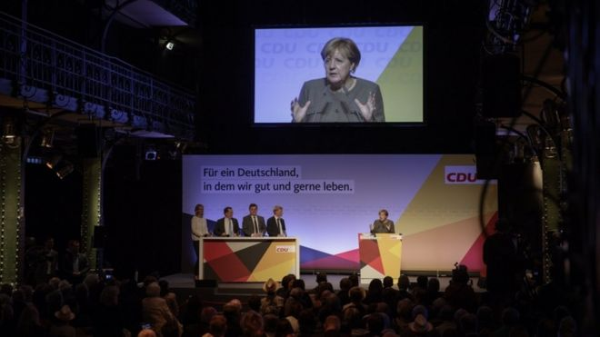 CDU politicians watch Merkel on stage in front of an audience in closed auditorium