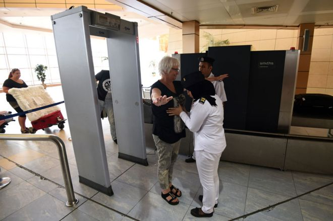 A woman is patted down at an Egyptian airport