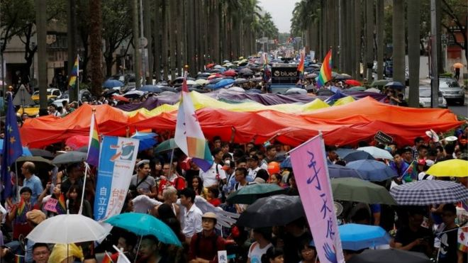 Participants hold a giant rainbow flag as they take part in the lesbian, gay,