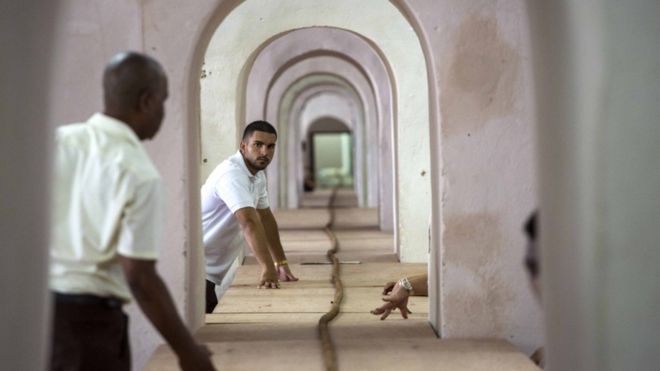 Workers help Cuban cigar roller Jose Castelar, hand roll a 90-meter cigar, stretching through many rooms, in Havana, Cuba, Friday, Aug. 12, 2016