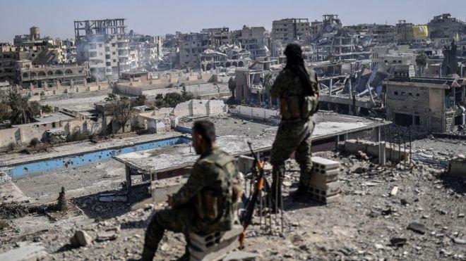 Suriye Demokratik Güçleri savaşçıları yüksek bir binanın üzerinden yıkılmış kente bakıyor