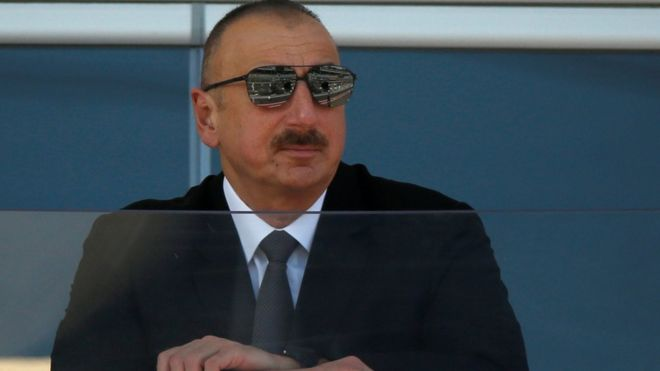Azerbaijan's President Ilham Aliyev watches a parade in Baku on 25 June