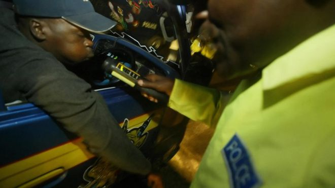 A Kenyan police-officer tests the alcohol-intake of a driver in this 23, December 2005 photo in Nairobi