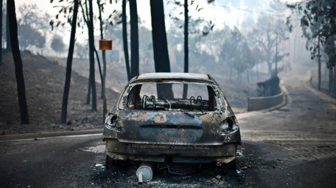 A burnt car on a road after a wildfire in Pedrogao, in central Portugal.