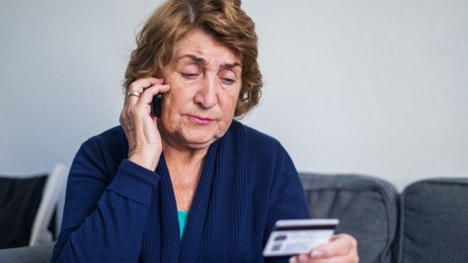 Idosa segura um cartão enqianto fala ao telefone