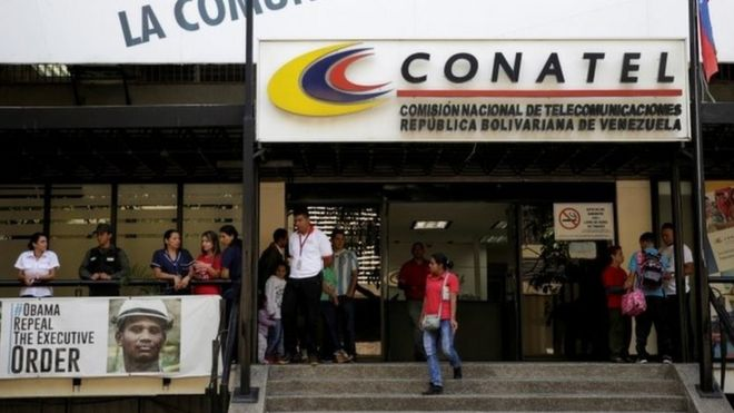 A woman walks out from the building of the National Commission of Telecommunications (CONATEL)