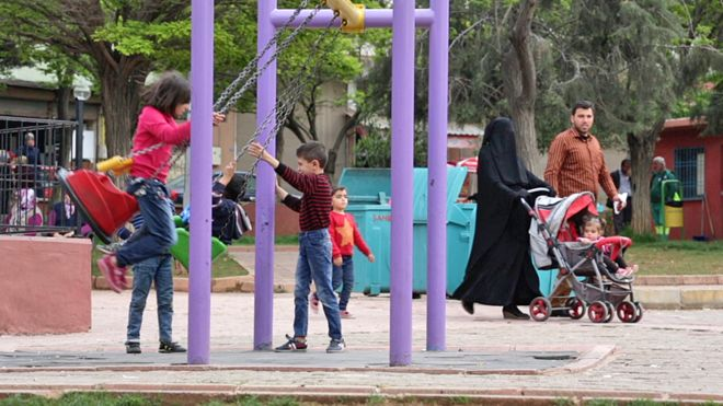 Children playing in a predominantly Syrian neighbourhood in Gaziantep, where a family walk past with the mother wearing a black veil