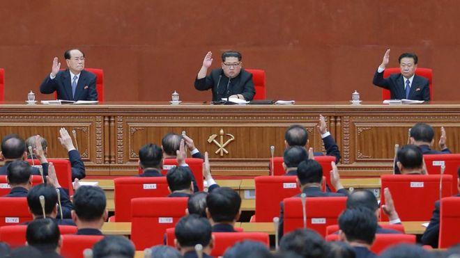 金正恩(中)在朝鮮勞動黨七屆三中全會上舉手錶決議案(20/4/2018)