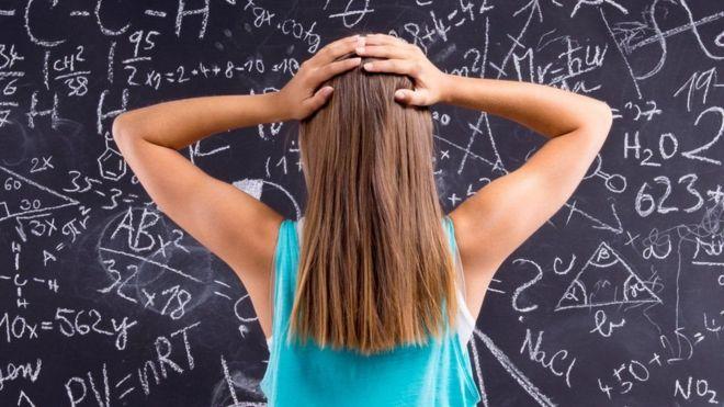 Mulher em frente a operações matemáticas no quadro